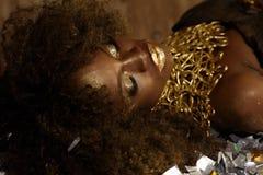 La mujer afroamericana joven atractiva con maquillaje del oro y los accesorios que mentían en confeti brillante del fondo cerraro Imagen de archivo libre de regalías