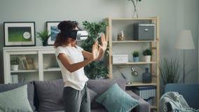 La mujer afroamericana joven está disfrutando de experiencia con los vidrios aumentados de la realidad que llevan las auriculares almacen de metraje de vídeo