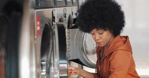 La mujer afroamericana joven se sienta delante de una lavadora y carga la lavadora con el lavadero sucio Autoservicio almacen de video