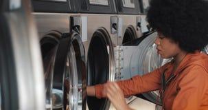 La mujer afroamericana joven se sienta delante de una lavadora y carga la lavadora con el lavadero sucio Autoservicio metrajes