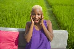 La mujer afroamericana negra atractiva y feliz joven al aire libre en el fondo del campo de hierba verde que parece excitado y ju foto de archivo libre de regalías