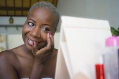 La mujer afroamericana negra feliz y atractiva joven envuelta en la toalla que aplica los cosméticos del maquillaje usando poner  imagen de archivo