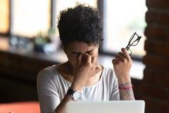 La mujer afroamericana que saca los vidrios, siente la fatiga visual imágenes de archivo libres de regalías