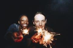 La mujer afroamericana y un hombre caucásico juntan jugar con la celebración de las bengalas y el concepto festivo del partido imagenes de archivo
