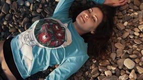 La mujer agradable, bonita miente con una sonrisa en su cara en una playa rocosa en un sweetshot metrajes
