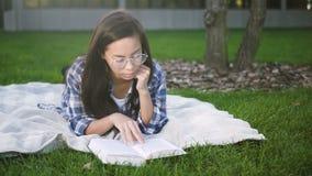 La mujer agradable de la raza mixta está mintiendo en la tela escocesa y la hierba cerca de campus metrajes