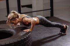 La mujer agradable joven trabajadora está haciendo el ejercicio para el ABS imagen de archivo