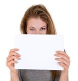 La mujer agradable sostiene la hoja de papel en blanco Imagenes de archivo