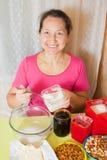 La mujer agrega el azúcar en plato Imagen de archivo