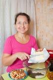 La mujer agrega la margarina en plato Fotografía de archivo libre de regalías
