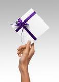 La mujer aislada da sostener la actual caja blanca del día de fiesta con la cinta púrpura en un fondo blanco Foto de archivo libre de regalías