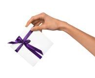 La mujer aislada da sostener la actual caja blanca del día de fiesta con la cinta púrpura en un fondo blanco Imagen de archivo libre de regalías