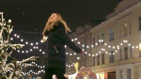 La mujer alegre baila al aire libre bajo caída de la nieve La señora feliz salta y hace girar alrededor en la calle metrajes