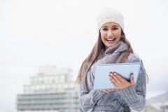 La mujer alegre con invierno viste en usar su tableta Fotografía de archivo libre de regalías