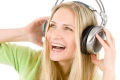 La mujer alegre con los auriculares escucha la música Imagen de archivo libre de regalías