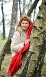 La mujer alegre con los costes de una bufanda del rojo que se inclinan contra un abedul en la madera Imagen de archivo libre de regalías