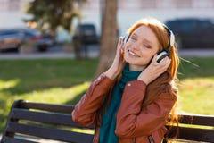 La mujer alegre contenta que escuchaba la música con los ojos se cerró Fotografía de archivo libre de regalías