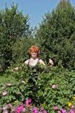 La mujer alegre cuida para las flores en su jardín Fotografía de archivo