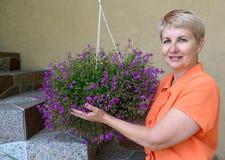 La mujer alegre de los años medios apoya un escondrijo-pote con las flores decorativas un lobelia Fotos de archivo libres de regalías