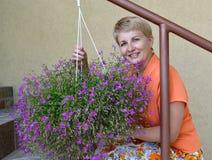 La mujer alegre de los años medios se sienta en una escalera y apoya un escondrijo-pote con las flores decorativas un lobelia Imagen de archivo libre de regalías