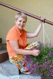 La mujer alegre de los años medios sienta en una escalera con las flores decorativas un lobelia Imagen de archivo libre de regalías
