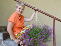 La mujer alegre de los años medios sienta en una escalera con las flores decorativas un lobelia Imagen de archivo