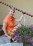 La mujer alegre de los años medios sienta en una escalera con las flores decorativas un lobelia Imagenes de archivo