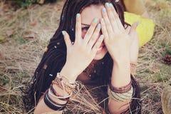La mujer alegre del estilo del indie con el peinado de los dreadlocks, se divierte que se cierra la cara con las manos Imagen de archivo
