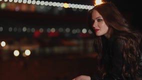 La mujer alegre del pelirrojo se está colocando en el fondo de las luces de la ciudad de la noche almacen de video