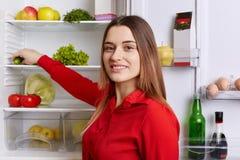 La mujer alegre en blusa roja con aspecto agradable se coloca cerca del refrigerador abierto, elige los productos necesarios para imágenes de archivo libres de regalías