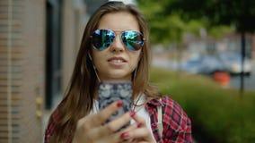 La mujer alegre encantadora en vidrios frescos escucha la música por los auriculares almacen de video