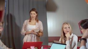 La mujer alegre está contestando en cuestiones de sus colegas durante su discurso metrajes