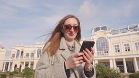 La mujer alegre está viendo las fotos y está leyendo SMS en teléfono móvil al aire libre almacen de video