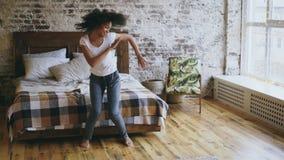 La mujer alegre joven de la raza mixta atractiva se divierte que baila cerca de cama en casa Imagenes de archivo