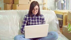 La mujer alegre joven del retrato utiliza el ordenador portátil que se sienta en el sofá después de trasladarse a un apartamento  metrajes