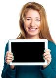 La mujer alegre joven está mostrando la tableta en blanco Fotos de archivo libres de regalías