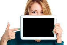 La mujer alegre joven está mostrando la tableta en blanco Foto de archivo libre de regalías