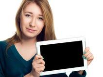 La mujer alegre joven está mostrando la tableta en blanco Fotografía de archivo libre de regalías