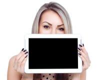 La mujer alegre joven está mostrando la tableta en blanco Fotos de archivo
