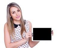 La mujer alegre joven está mostrando la tableta en blanco Imagenes de archivo