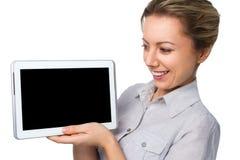 La mujer alegre joven está mostrando la tableta en blanco Imagen de archivo