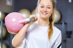 La mujer alegre joven lleva a cabo el kettlebell en el centro del gimnasio de la aptitud Fotografía de archivo libre de regalías
