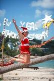 La mujer alegre linda salta en vestido y el sombrero rojos de santa en la playa tropical exótica Concepto del día de fiesta para  Foto de archivo