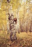 La mujer alegre mira hacia fuera de detrás un árbol Foto de archivo libre de regalías