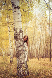 La mujer alegre mira hacia fuera de detrás un árbol Fotos de archivo libres de regalías