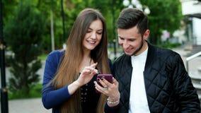 La mujer alegre muestra a hombre una foto, juego, uso, compras en línea metrajes