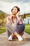 La mujer alegre que se colocaba con las piernas cruzó y disfruta de música Fotos de archivo libres de regalías