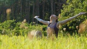 La mujer alegre que se sienta en el césped verde levanta feliz sus manos hasta el cielo en campo escénico en el fondo de la puest almacen de video