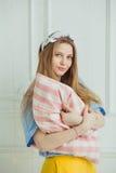 La mujer alegre sostiene la almohada en manos La muchacha fuera compone Imágenes de archivo libres de regalías