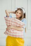 La mujer alegre sostiene la almohada en manos La muchacha fuera compone Imagen de archivo libre de regalías